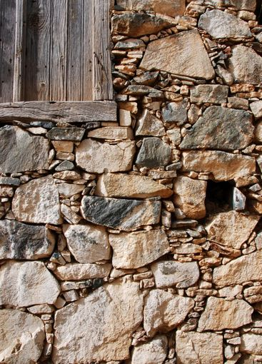 Old wooden door on a stoned wall