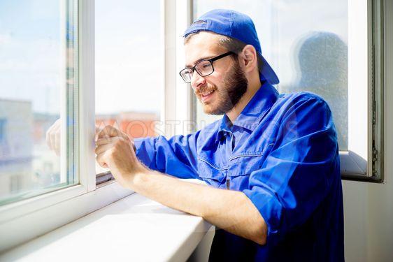 Construction worker installing window