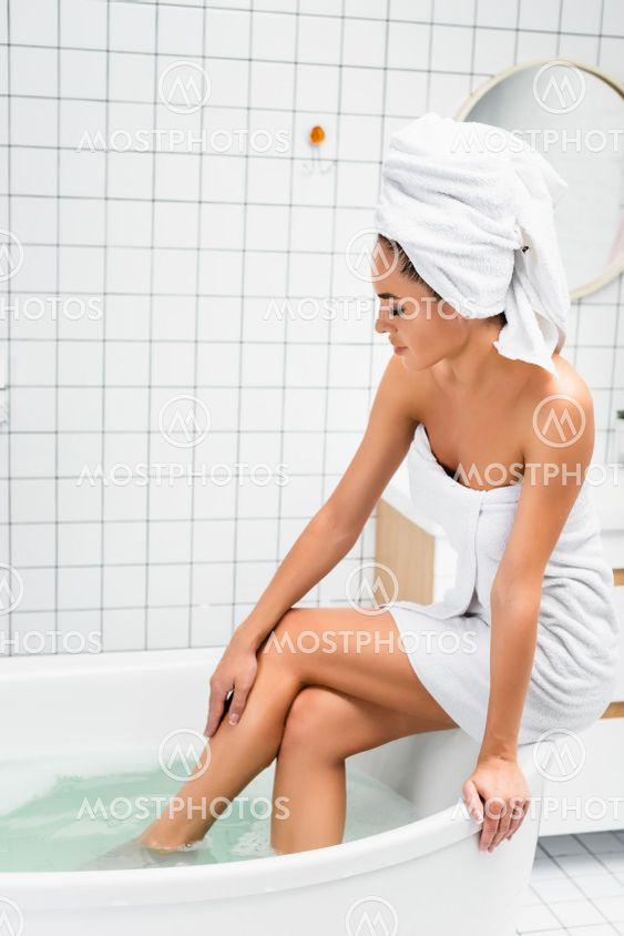 Woman in towels touching leg while sitting on bath with...