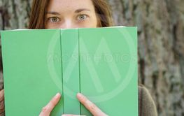 Young woman hiding behind a hardcover book