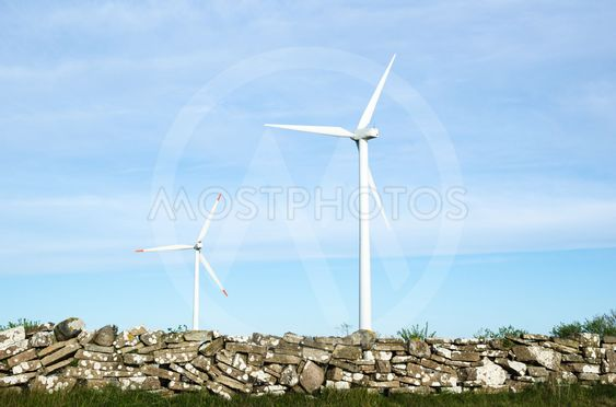 Two wind turbines by an old traditional stonewall at the...