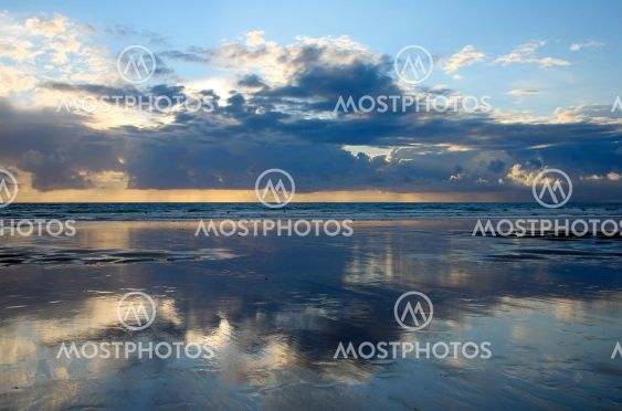 Cloud reflections on the beach at dusk.