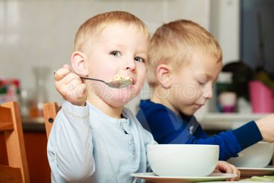 Boys kids children eating corn flakes breakfast meal at...