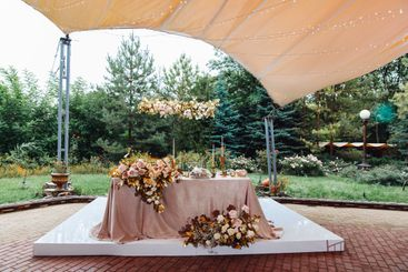 table of bride and groom in tent in the open air.