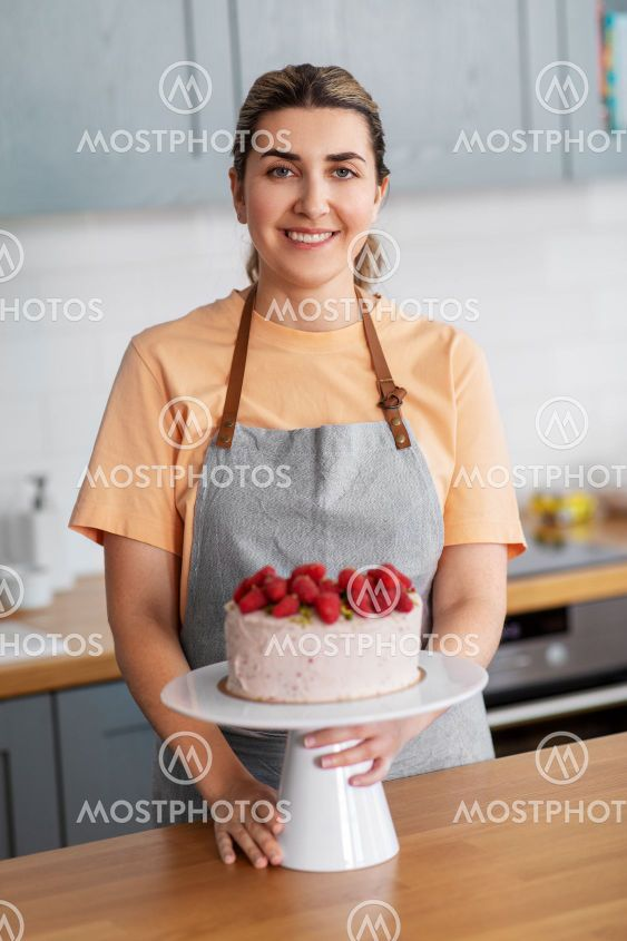 happy woman with raspberry cake on kitchen at home