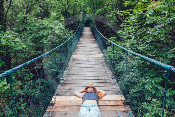 Young woman in the forest lying on the wooden bridge,...