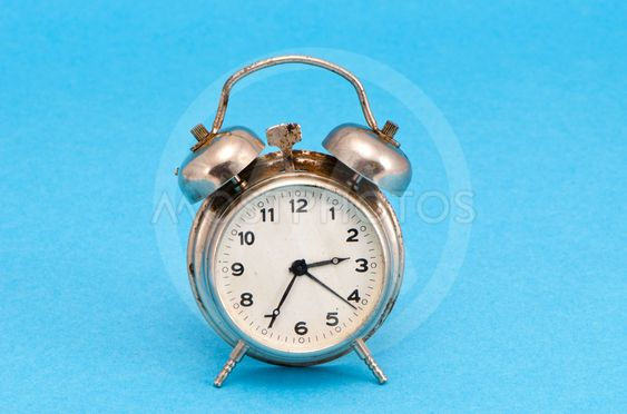 Retro grunge rusty alarm clock blue background