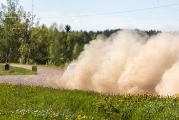 Rally racing car spraying dust and gravel behind.