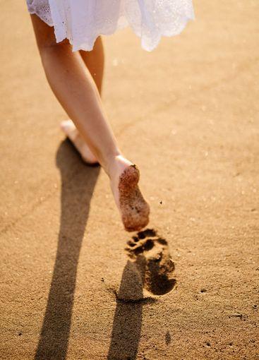 little feet leave footprints on sandy shore of sea....