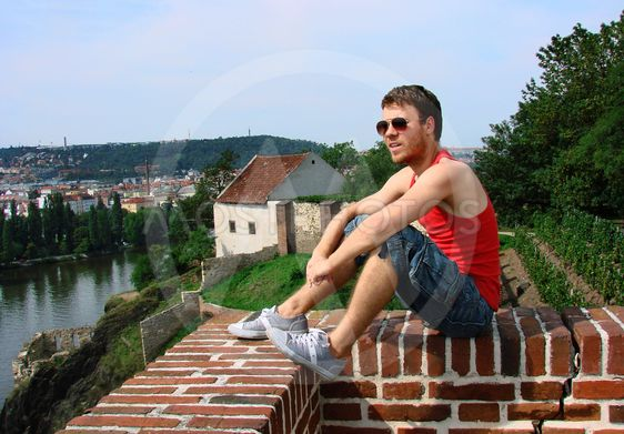 A guy sitting on a fence