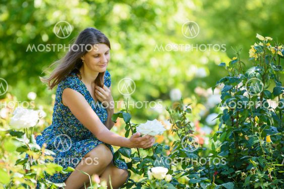 Girl in green garden admires white rose on bush