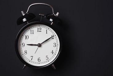 Alarm clock on a black background in Low-key lighting