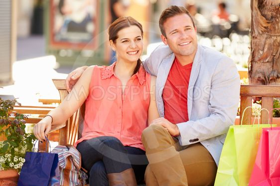 Young Couple Resting With Shopping Bags Sitting In Mall