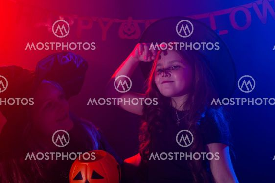 Funny child girl and woman in witches costumes for...
