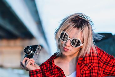 girl posing with a camera under the bridge
