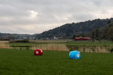 Rolls of hay painted as billliard balls on a field