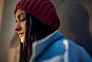 Close up shot of sad young female in red knitted cap