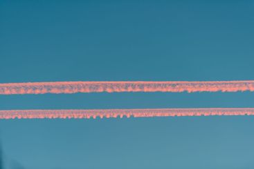 airplane contrail in the middle of the sky at sunset