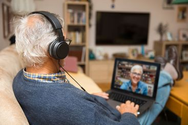 Modern elderly man siting at home and having online...