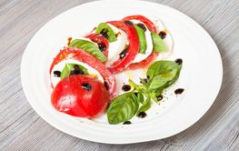sliced mozzarella and tomato with basil leaves