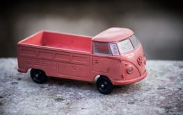 Top view of orange Volkswagen van toy miniature in outdoor