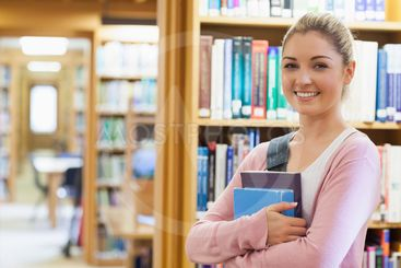 Student standing at the library holding books