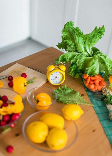 Yellow cooking timer between fresh cooking ingredients -...