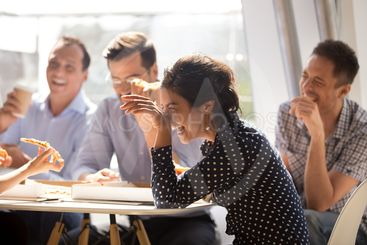 Indian woman laughing eating pizza with diverse coworkers...