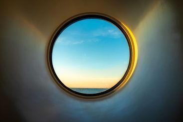 Havsutsikt från runt fönster i båt hytt.