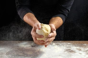 Male hands chef close-up, knead the dough, cook the...