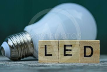 word LED made of wooden letters and  light bulb