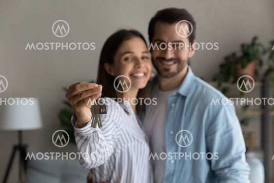 Happy married couple holding keys from new bought house,...