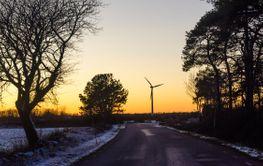Vinterväg med vindkraftverk i solnedgången