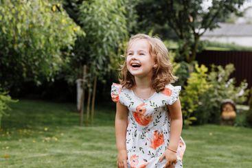 Little happy girl having fun in green summer park. happy...