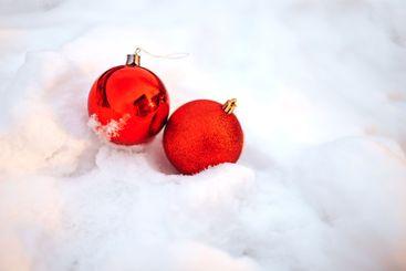 Two Christmas balls on snow.