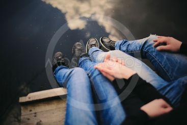 Loving couple sitting near river on bridge holding hands.