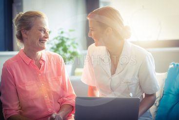 Female nurse and senior woman smiling while using laptop
