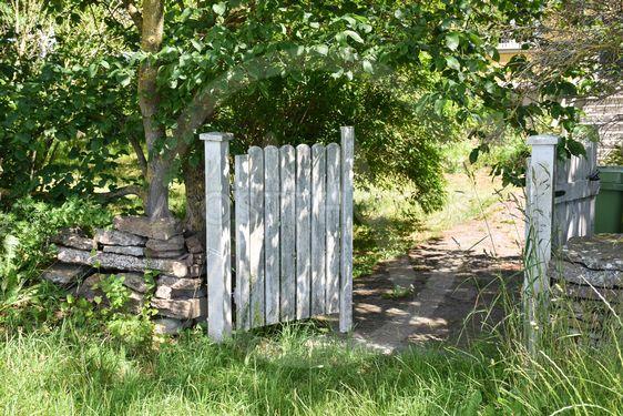 Öppen vit grrind till en trädgård