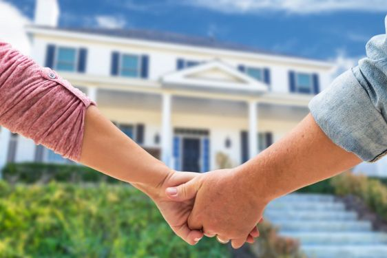Couple Holding Hands Approaching Front Door Of New House.