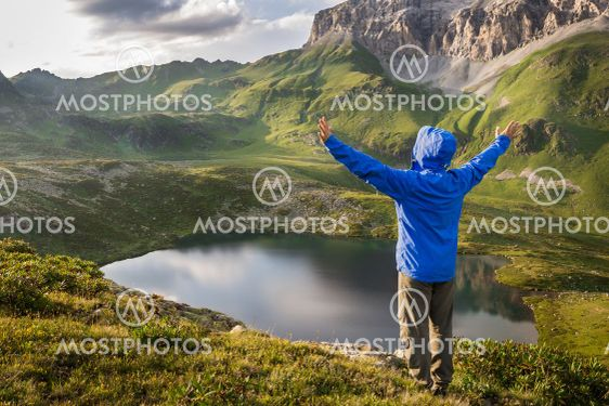 Hiker standing with raised hands near beautiful mountain...