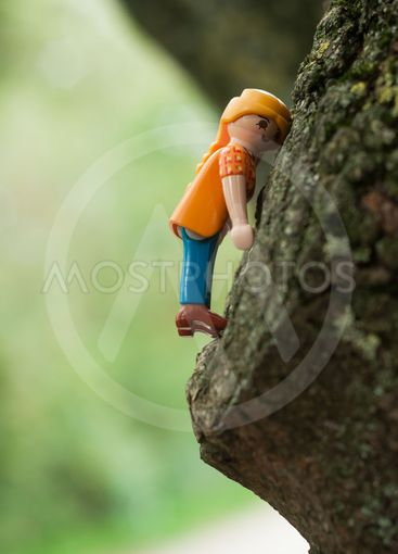 Playmobil characters climbing  on tree trunk  in outdoor