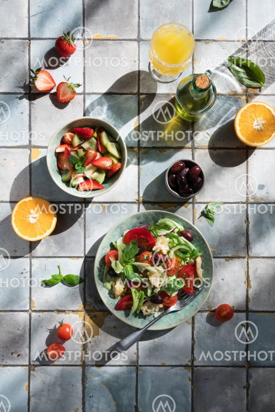 Mediterranean dishes at tiles table: vegetable and fruit...