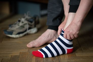 The man is putting colorful striped socks