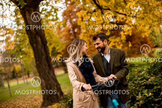 Young couple in the autumn park with electrical bicycle
