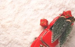 Red truck with Christmas trees and gift boxes in the snow