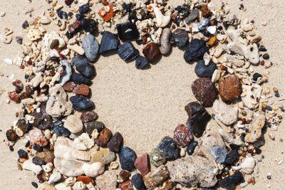 Stone arrangement as heart frame on the beach