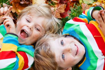 Two little kid boys laying in autumn leaves in colorful...