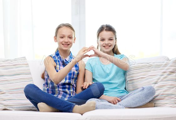 happy little girls showing heart shape hand sign