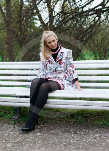 blonde girl sitting on a park bench