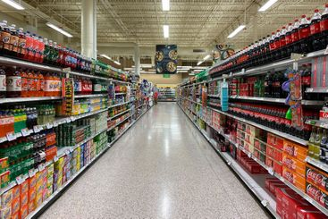 The beverage aisle of a grocery store with soft drink...